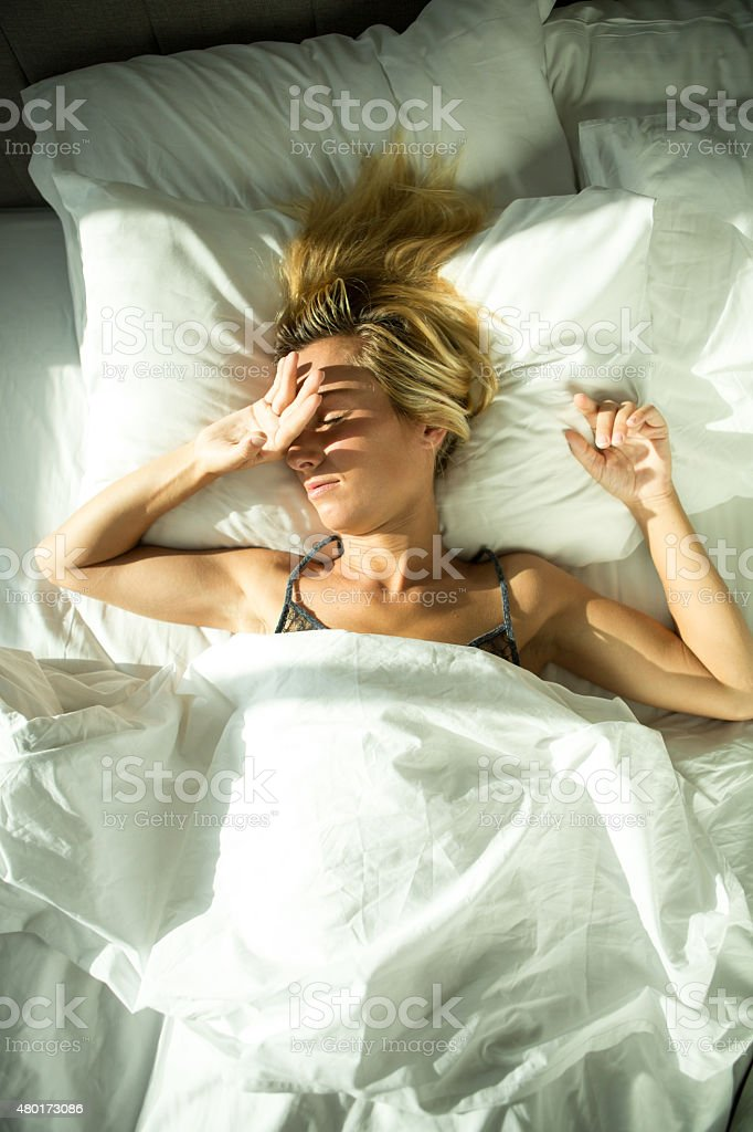 Girl awaked by sunlight coming in hotel room stock photo