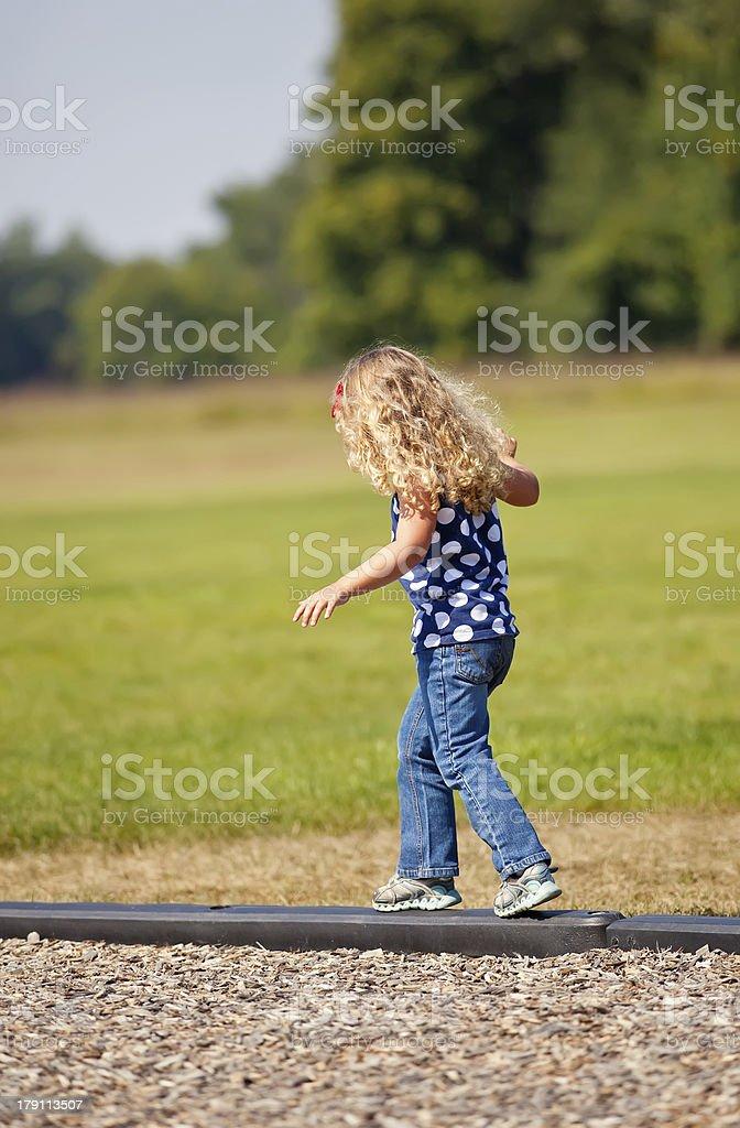 Girl Balancing on Curb at Park royalty-free stock photo