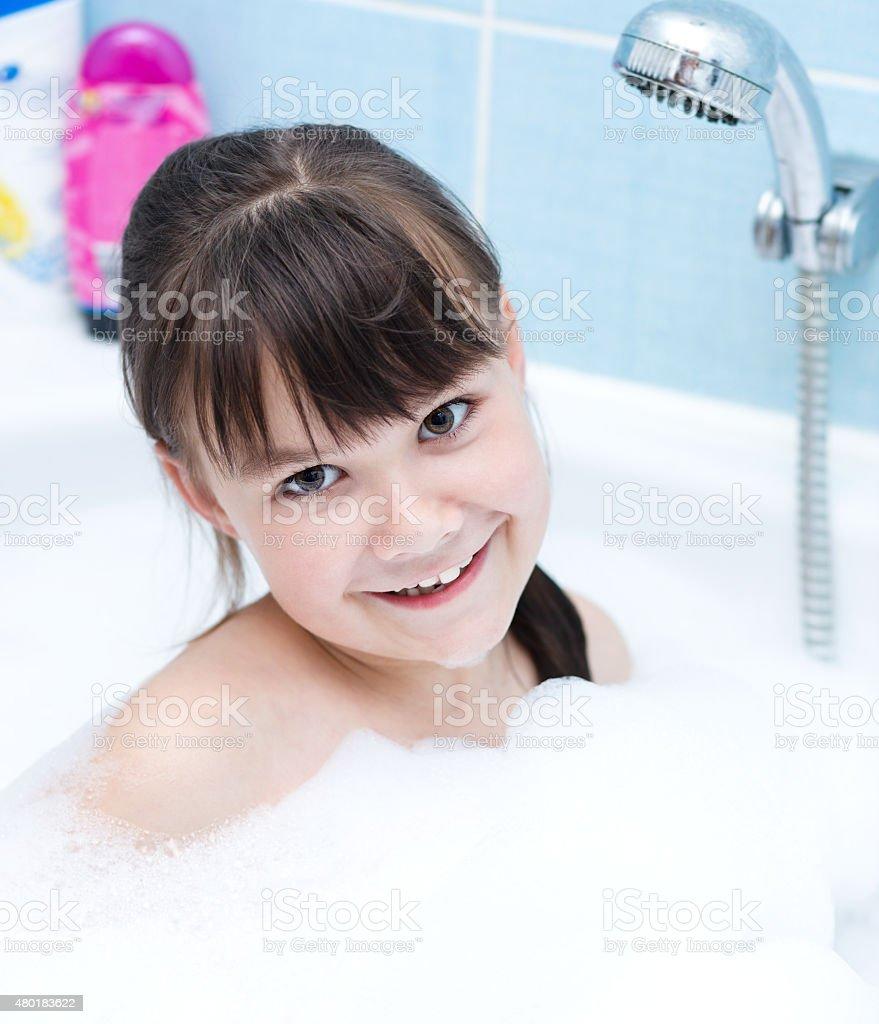 Girl bathes in a bathroom stock photo
