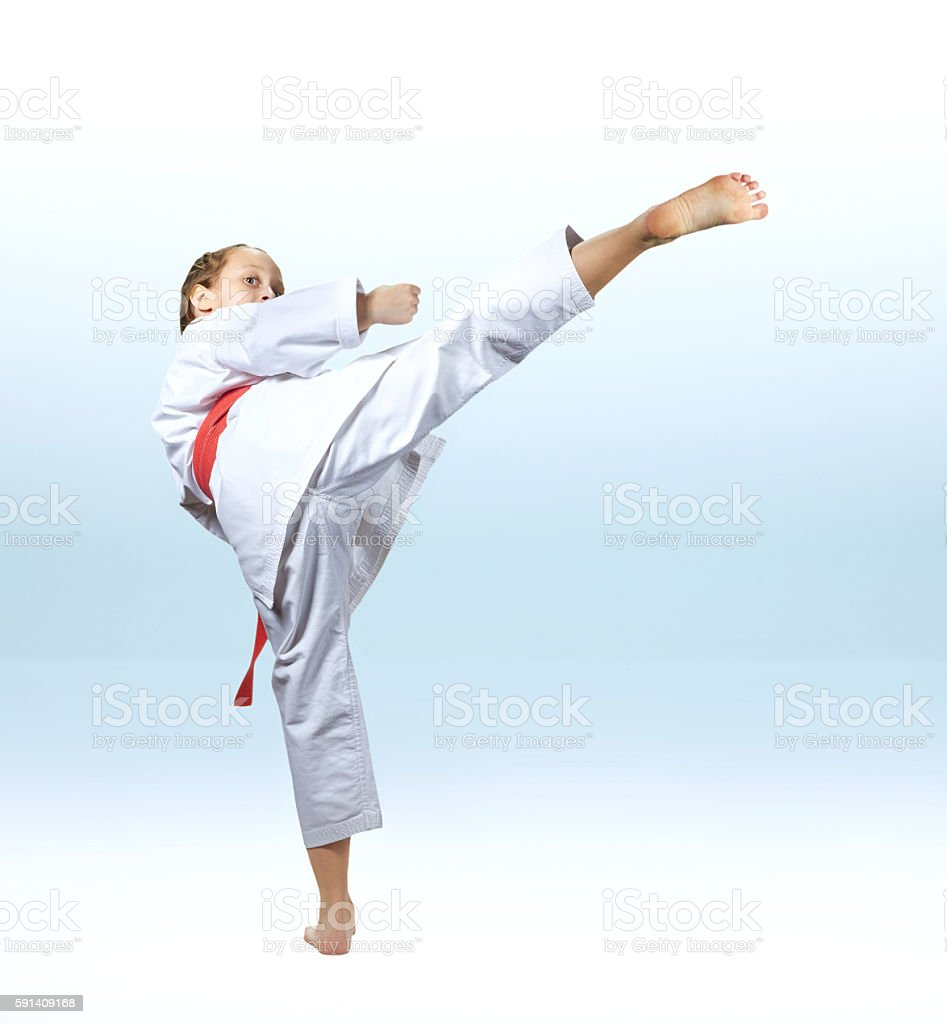Girl beats a high kick leg on the light background stock photo