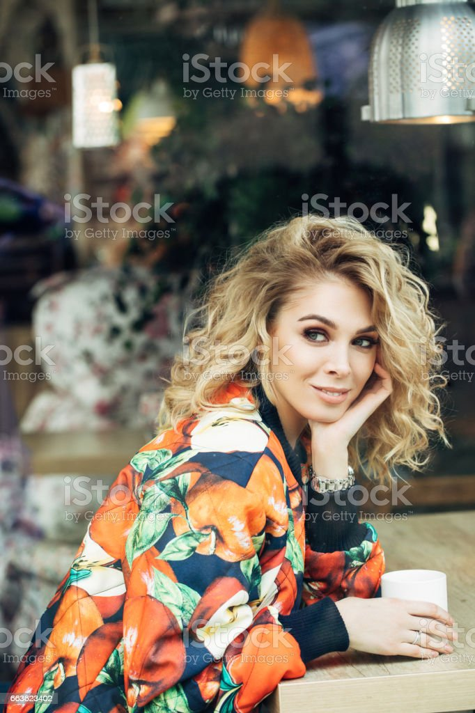 Girl behind the window in a cafe stock photo