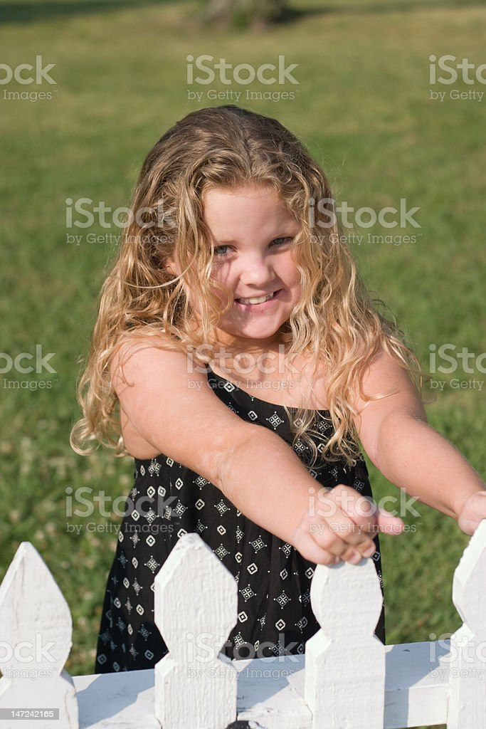 Girl behind white picket fence royalty-free stock photo