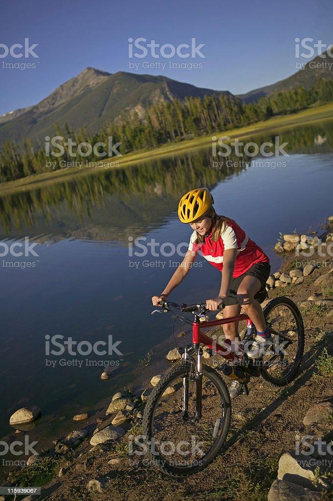 Girl Biking by Mountain Lake royalty-free stock photo