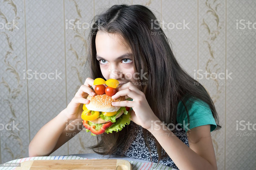 girl bites her teeth into a burger stock photo