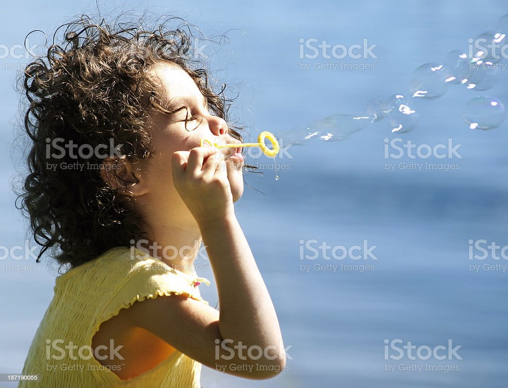 Girl Blowing Bubbles Into the Sun royalty-free stock photo