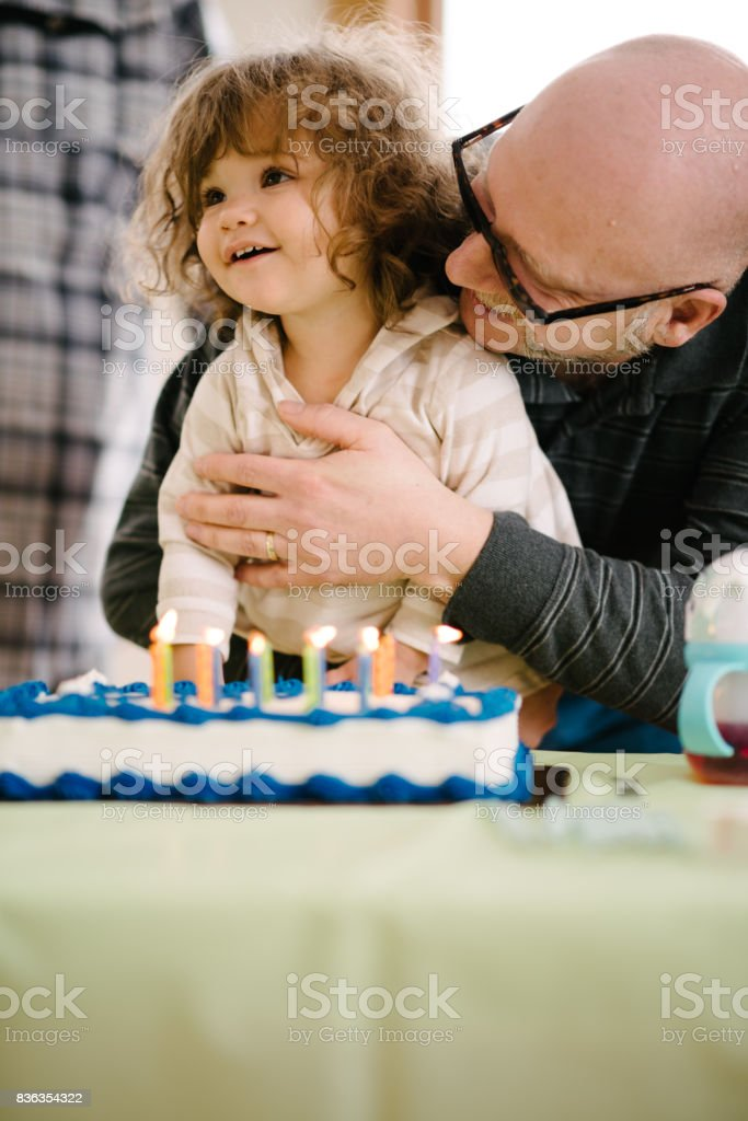 Girl blowing candles on cake stock photo