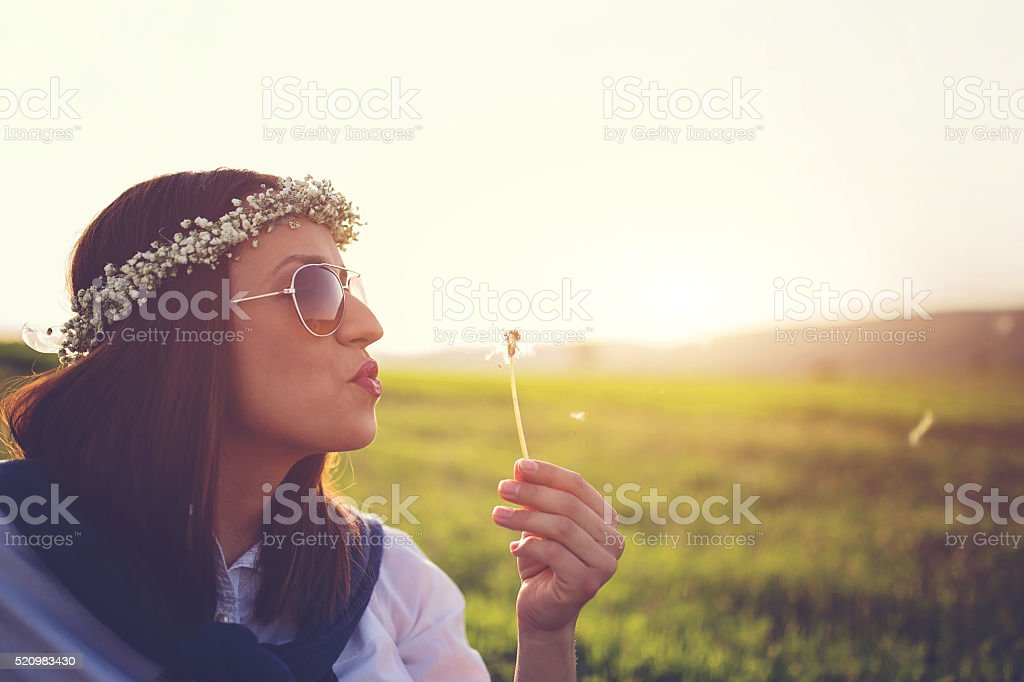 Girl blowing dadelion stock photo