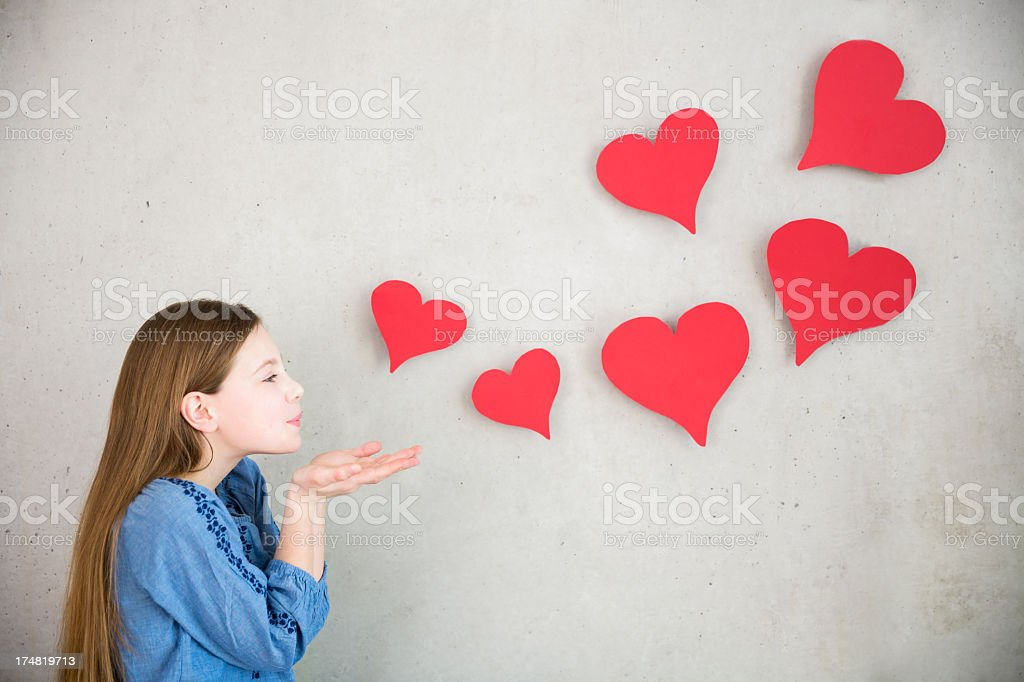Girl blowing hearts away stock photo
