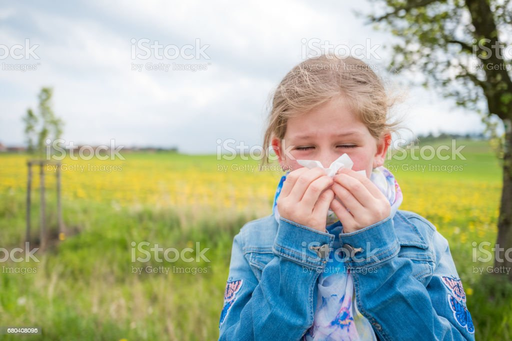 Young girl blowing her nose with closed eyes, suffering from allergy...