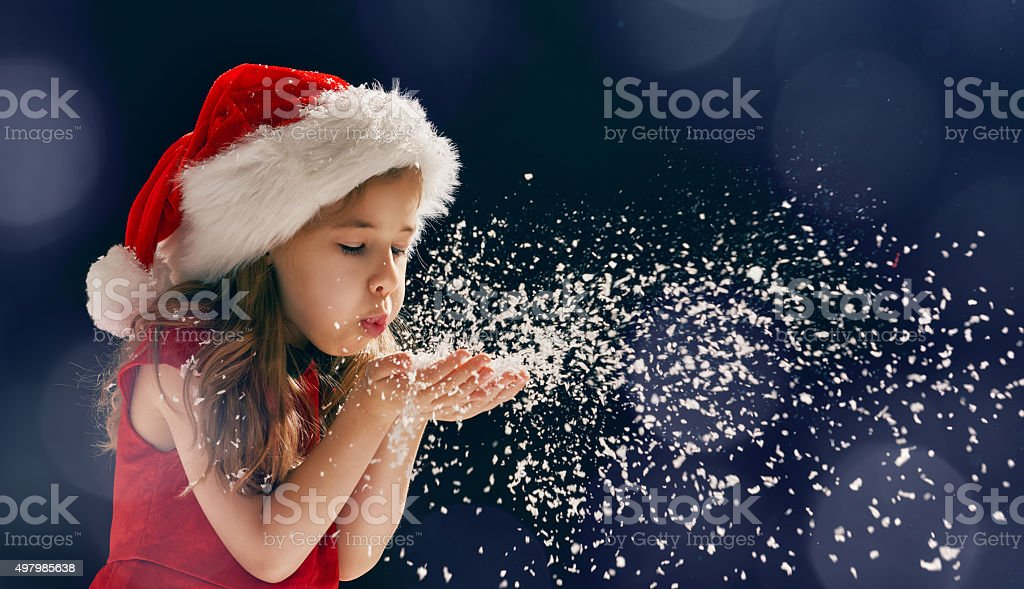 girl blowing on snow stock photo