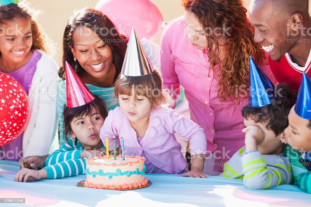 Girl blowing out birthday candles stock photo