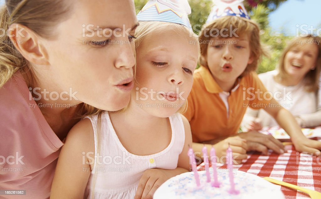 Girl blowing out candles on a birthday cake royalty-free stock photo
