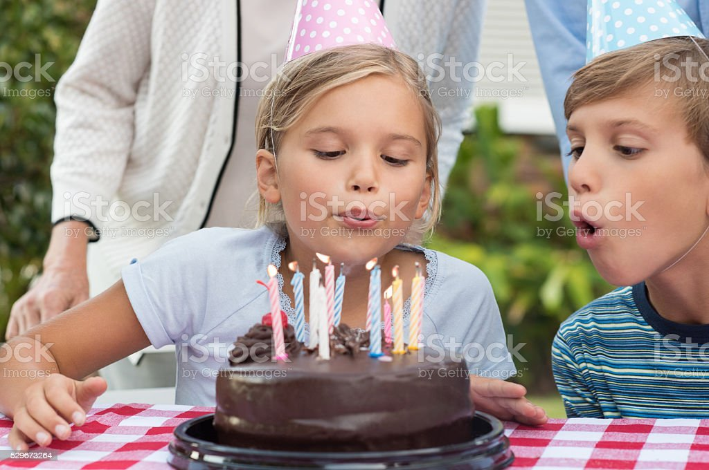 Girl blowing out the candles stock photo