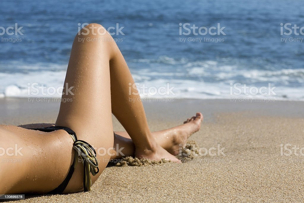 Girl body lying on  beach by the sea. royalty-free stock photo