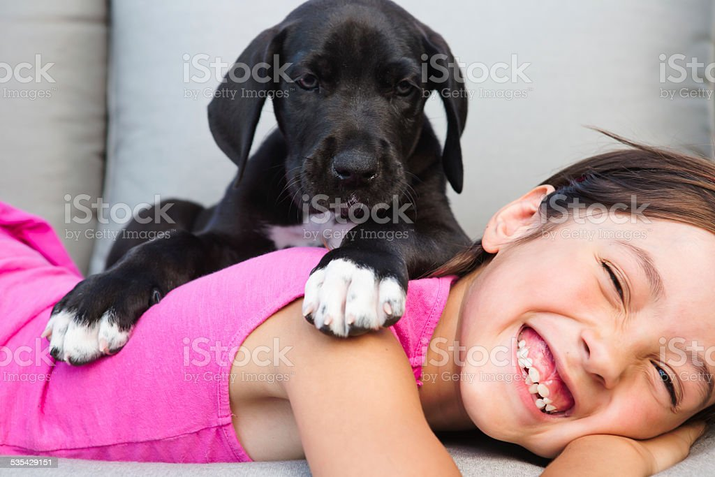 Girl bonding with puppy stock photo