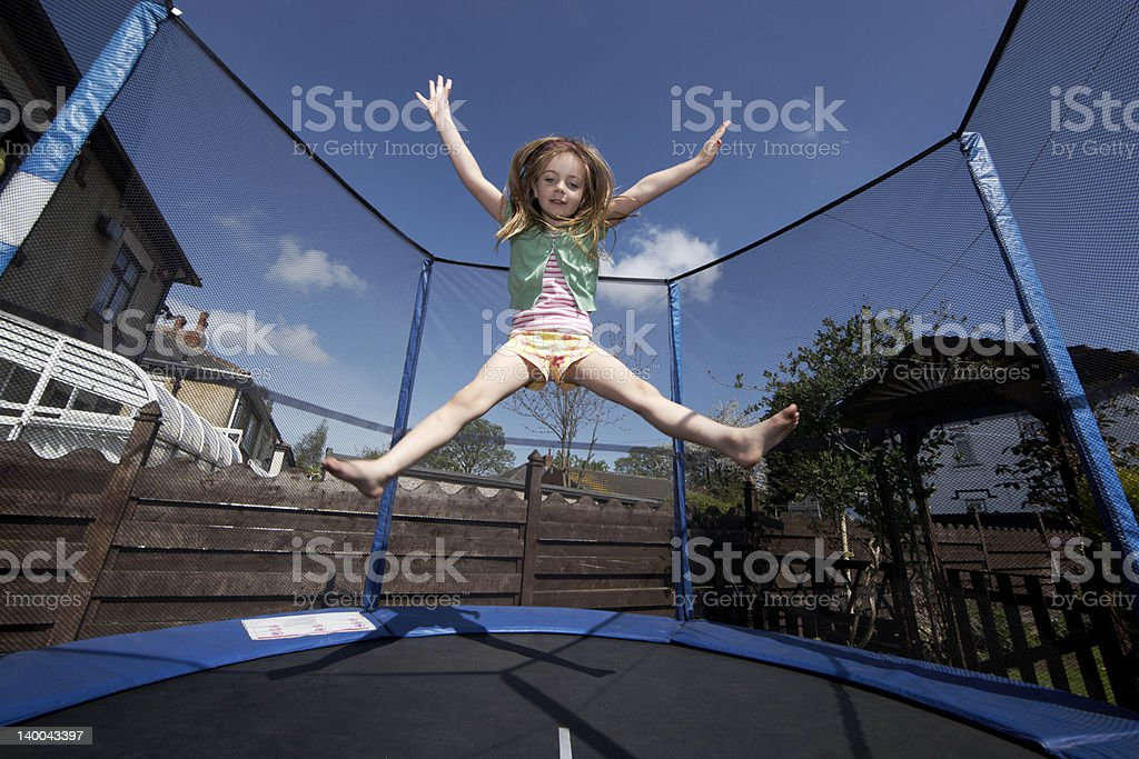Girl bouncing on trampoline stock photo