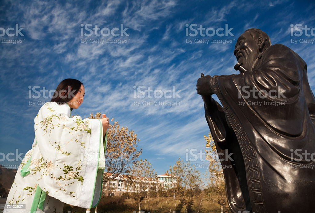 Girl bowed to Confucius stock photo