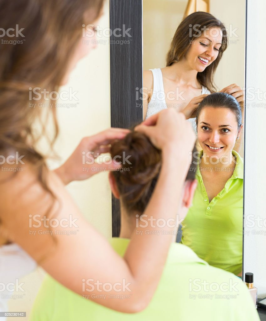 Girl brushing her friend at home stock photo