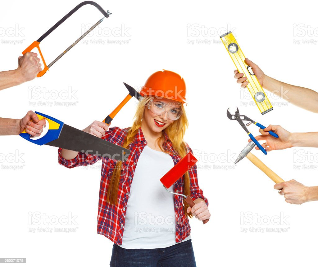 Girl builder and hands around her with building tools stock photo