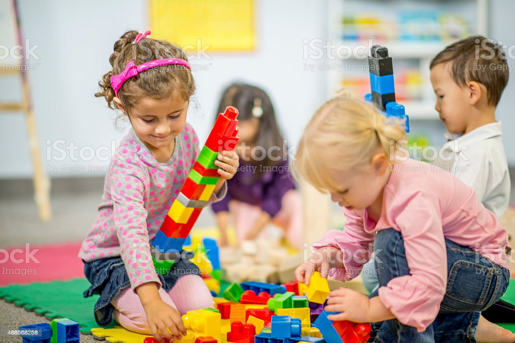 Girl Building a Tall Lego Tower stock photo
