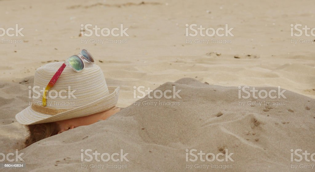 A girl buried in the sand on the beach in summer, a hat with glasses on her face stock photo