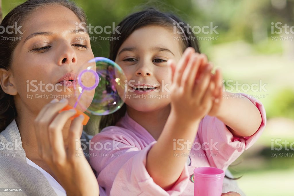 Girl bursting bubbles that her mother are blowing stock photo