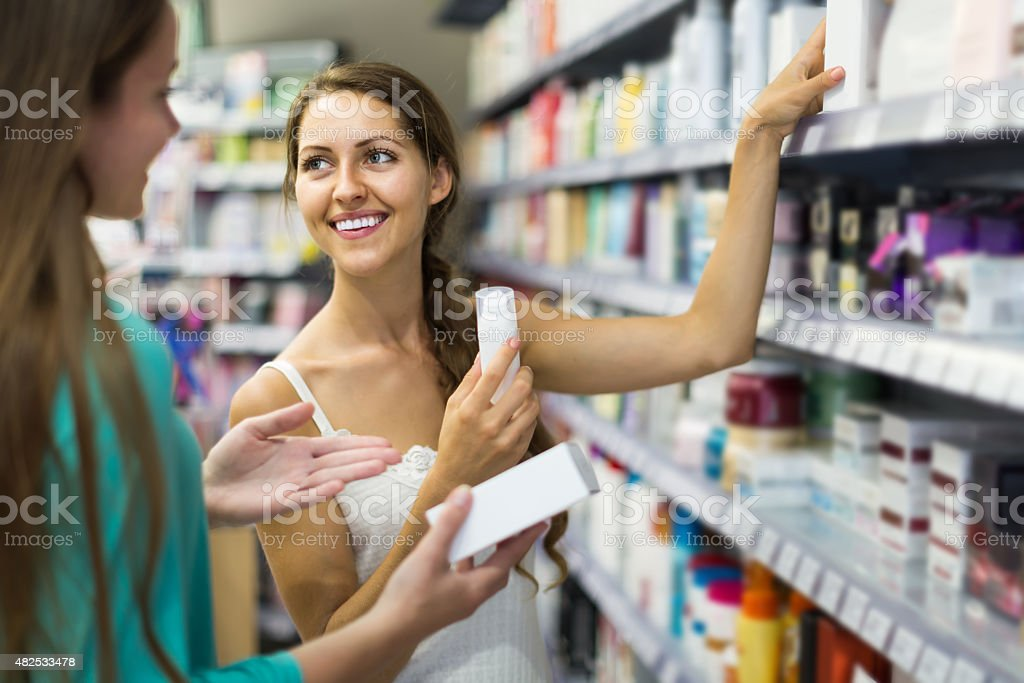 girl buying cosmetical cream in the shopping mall stock photo