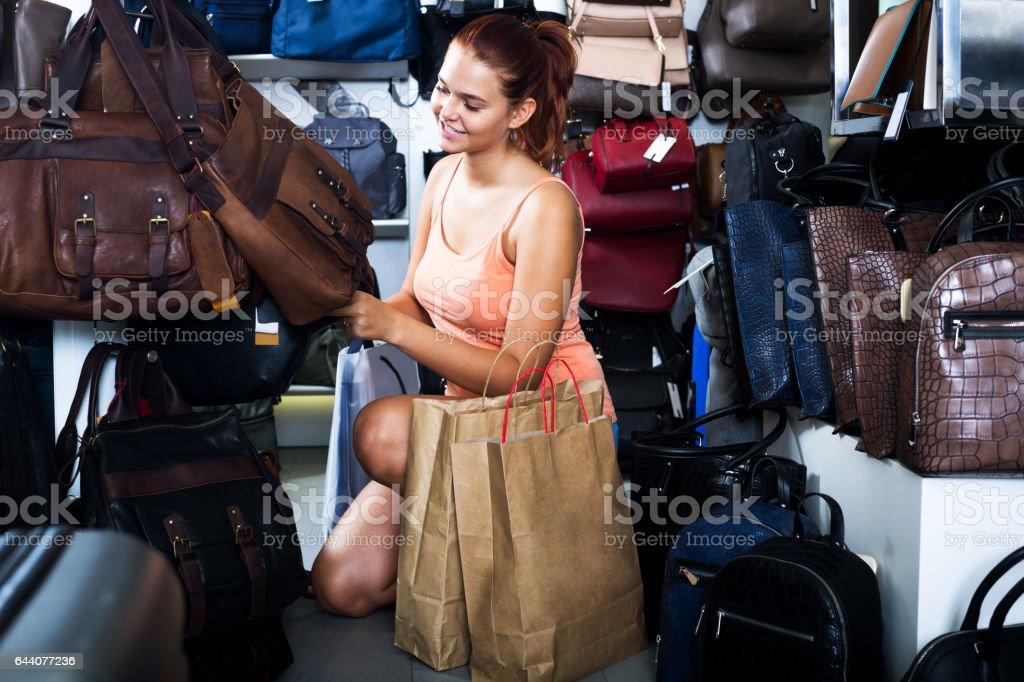 Girl buying handbag in fashion shop stock photo