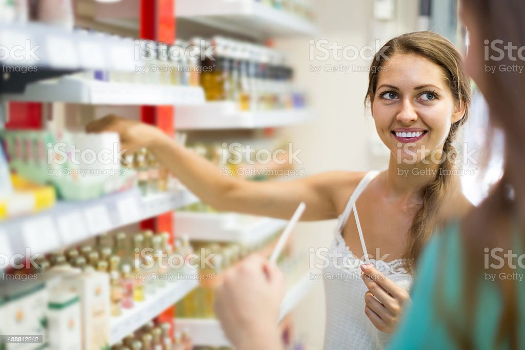 girl buying perfume in the shopping mall stock photo