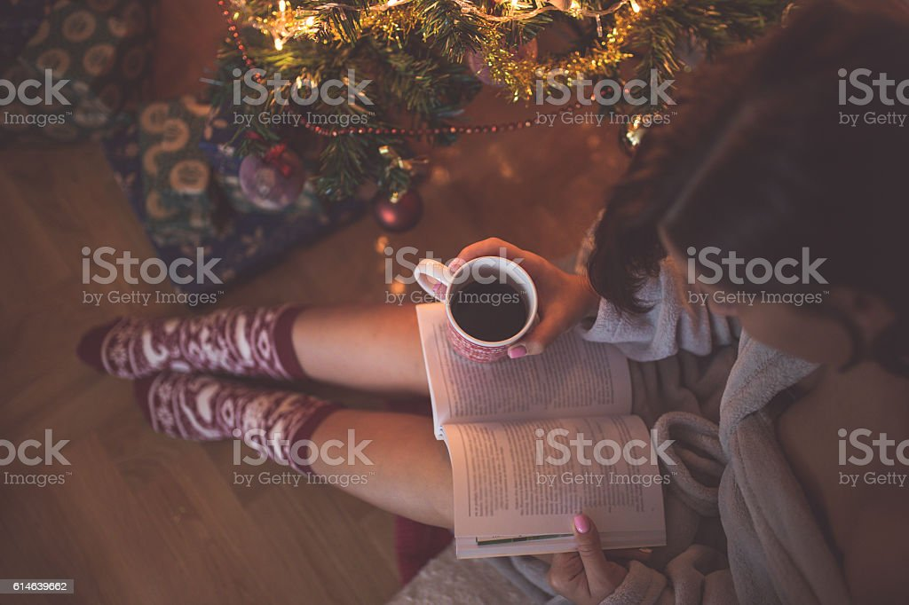 Girl by christmas tree with coffee cup reading a book stock photo