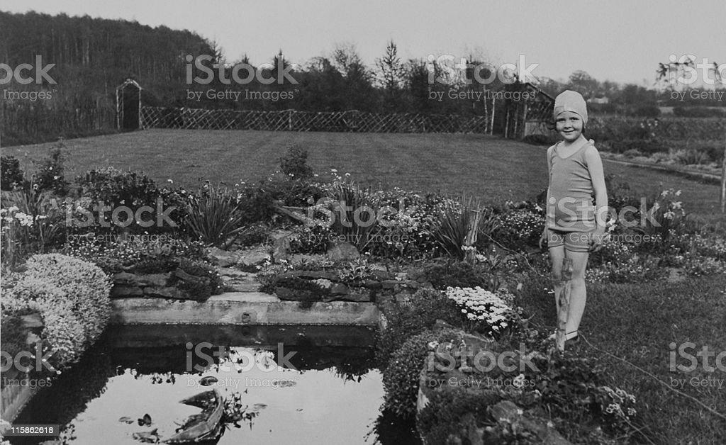 girl by garden pond 1930, retro stock photo