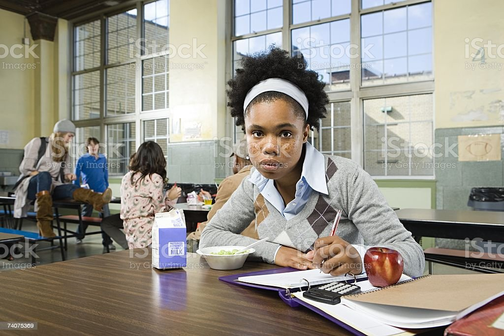 Girl by herself in cafeteria stock photo