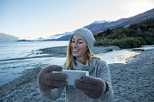 Girl by the lakeshore takes selfie using a smart phone