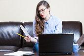 Girl calculating bills at home