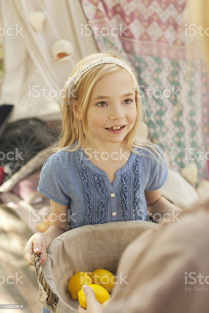 Girl carrying basket of lemons outdoors royalty-free stock photo