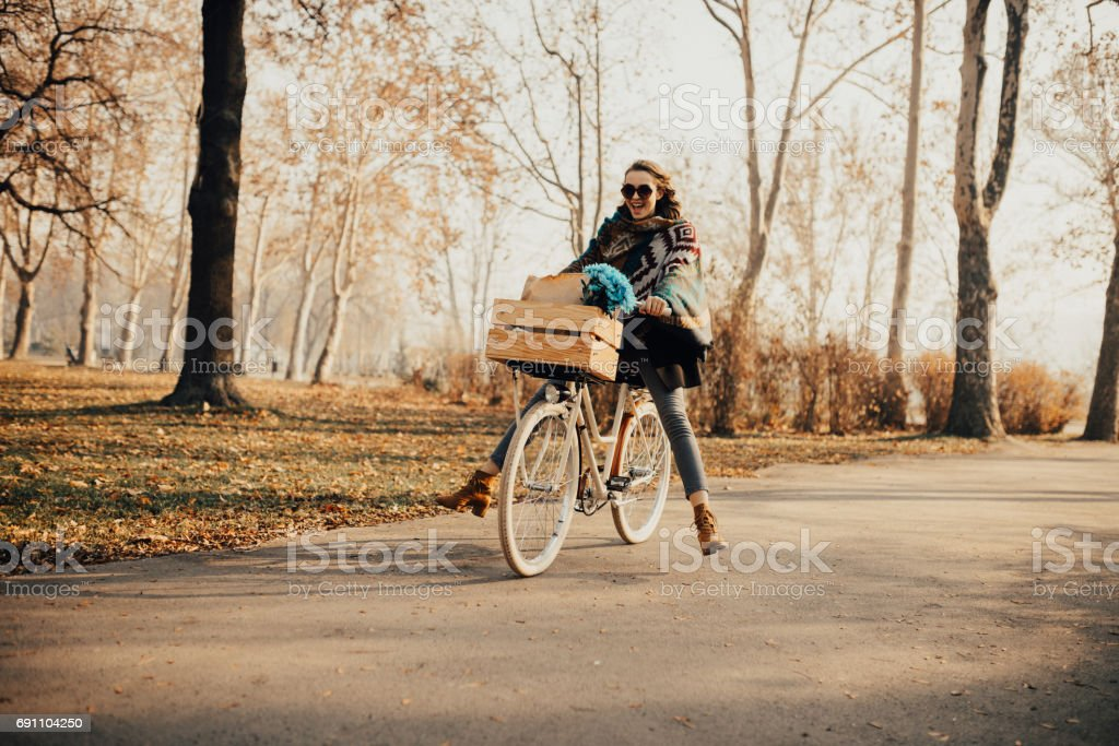 Girl carrying bouquet of flowers in the basket on the bike stock photo