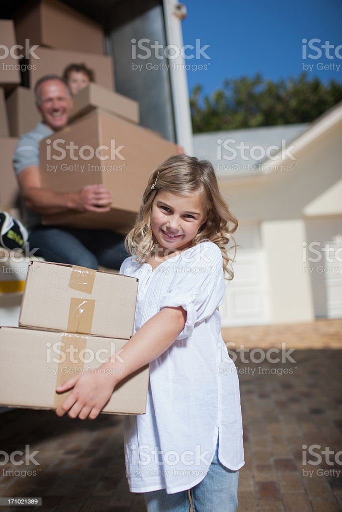 Girl carrying boxes  from moving van royalty-free stock photo