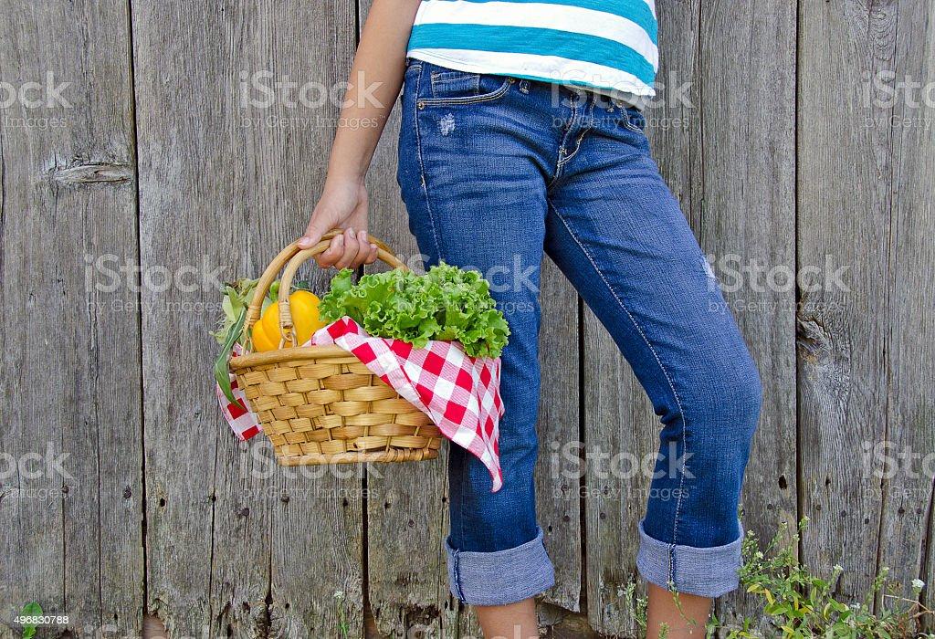 girl carrying fresh vegetables in basket stock photo
