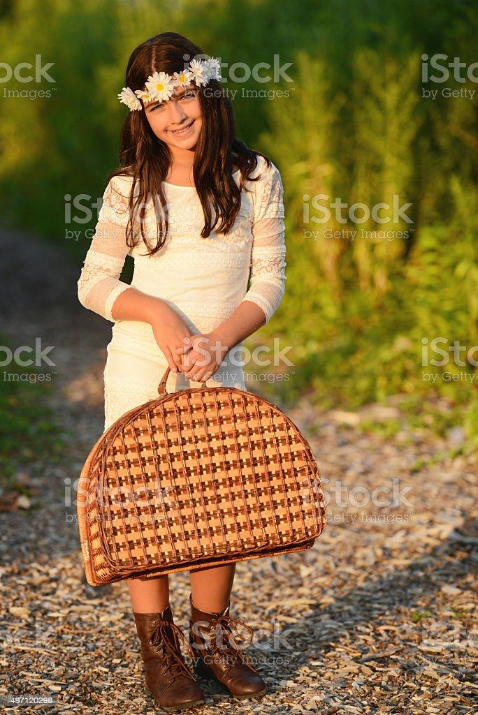 girl carrying vintage picnic basket stock photo