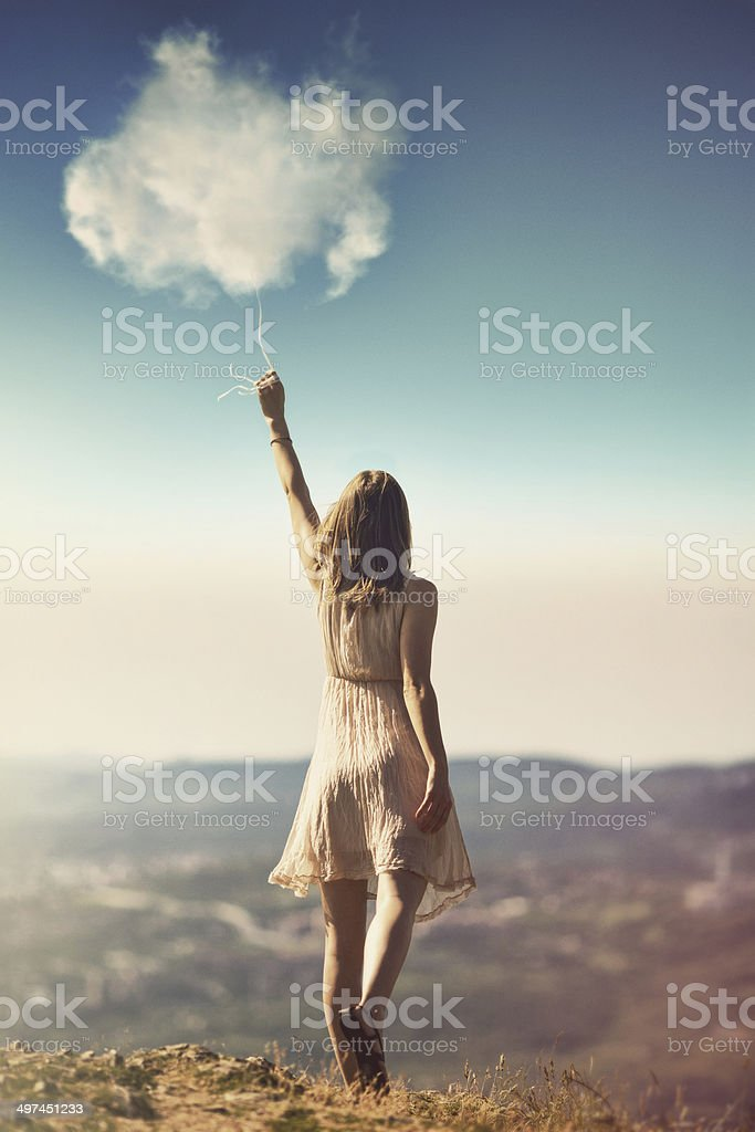 Girl catching clouds stock photo