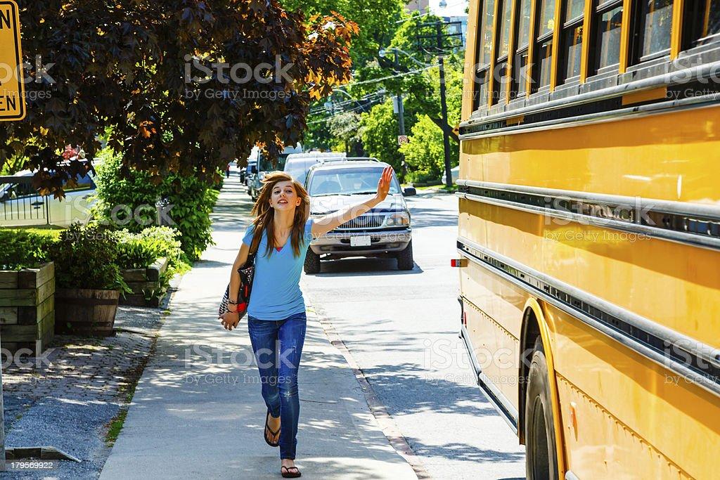Girl catching school bus stock photo