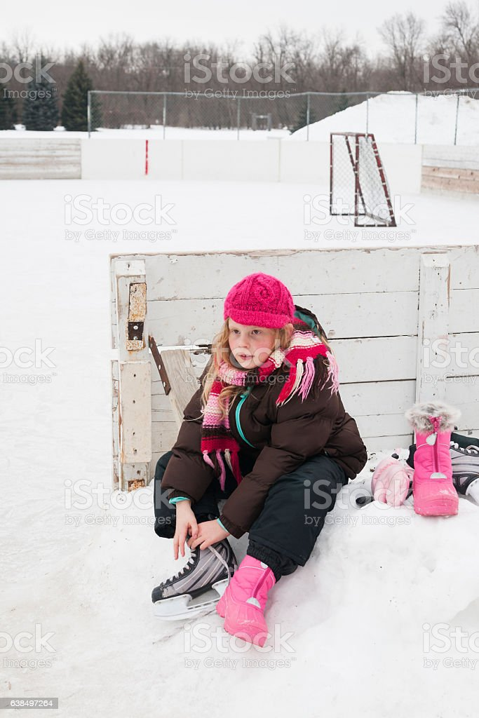 Girl changing into ice skates stock photo