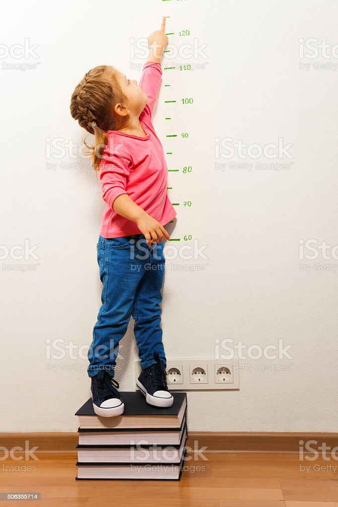Girl checking height on growth chart at four books stock photo