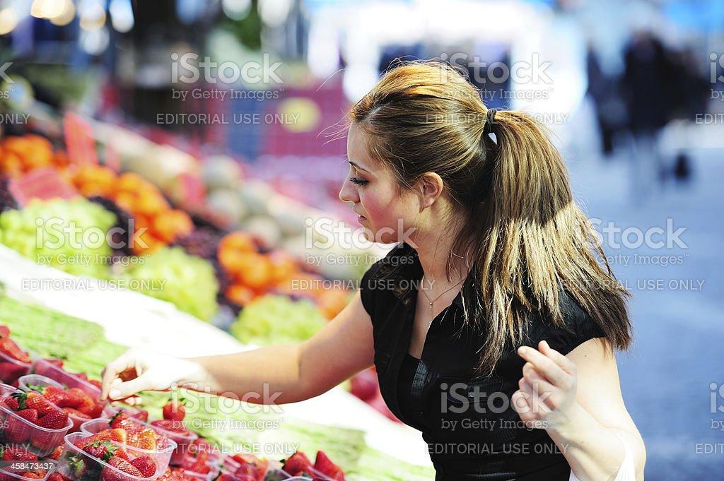 Girl checking strawberrys at market royalty-free stock photo