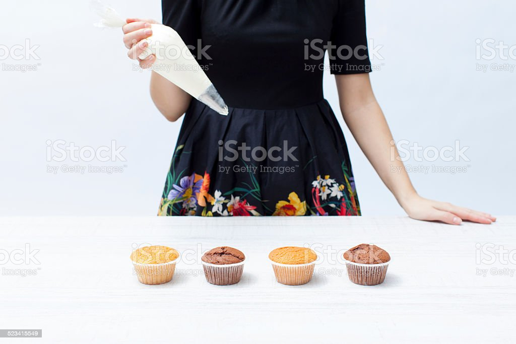 Girl chef with piping bag with the cream, cupcakes stock photo