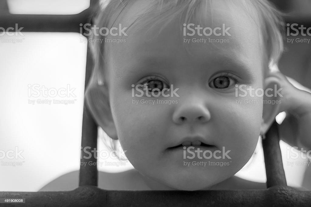 girl child behind bars stock photo