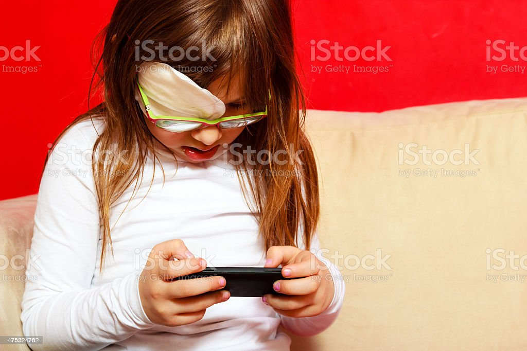 girl child in glasses playing games on smartphone at home stock photo