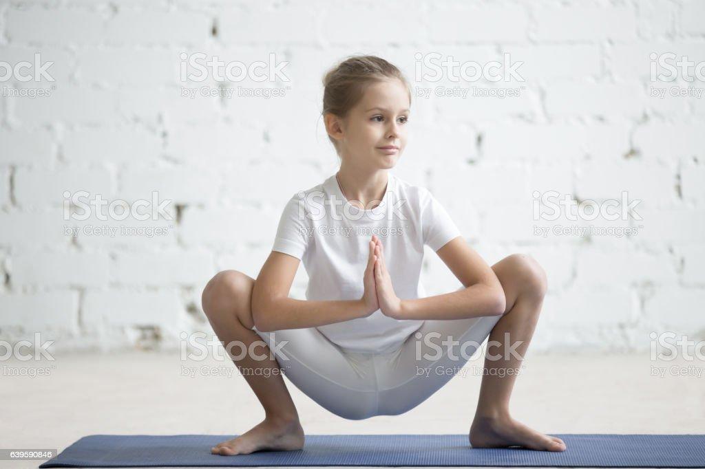 Girl child in Malasana pose, white studio background stock photo