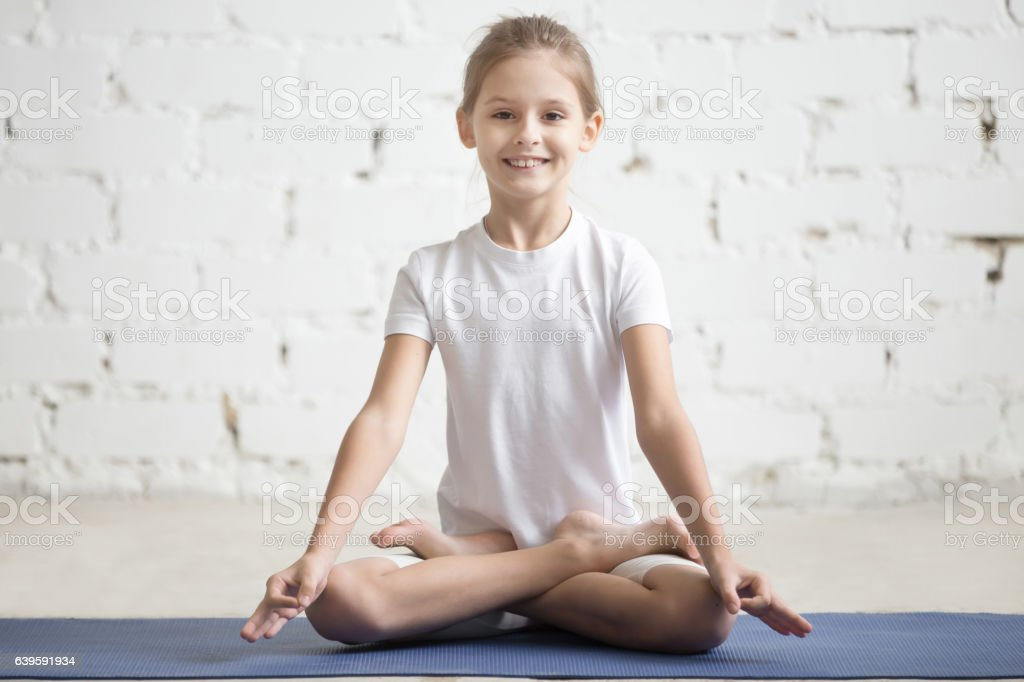 Girl child in Padmasana pose, white studio background stock photo