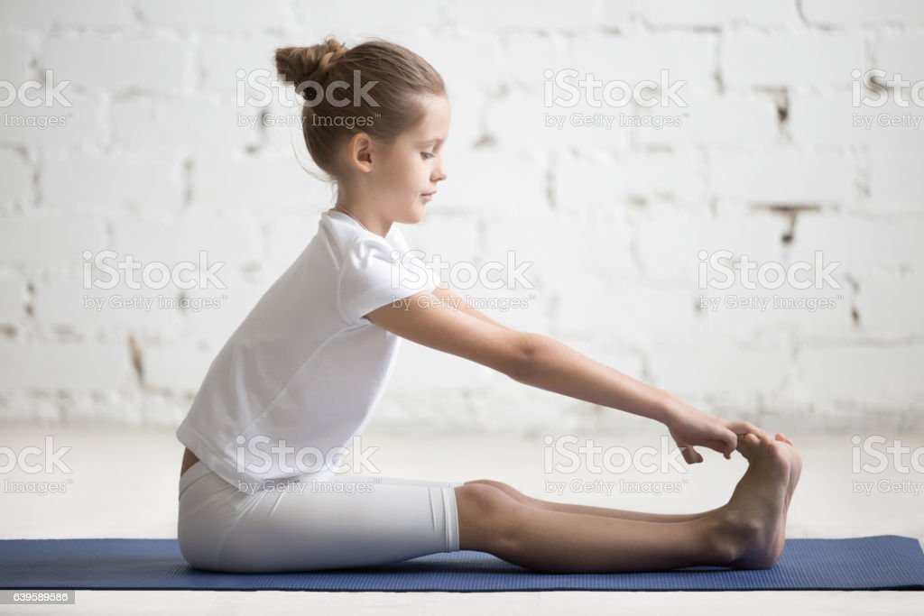 Girl child in paschimottanasana pose, white studio background stock photo